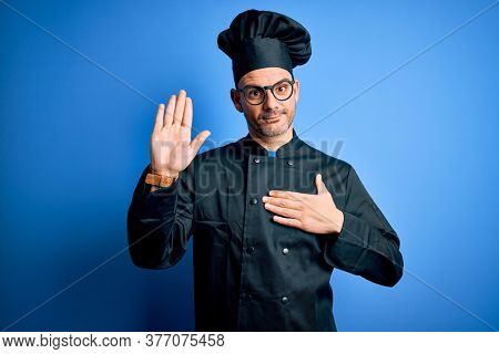Young handsome chef man wearing cooker uniform and hat over isolated blue background Swearing with hand on chest and open palm, making a loyalty promise oath