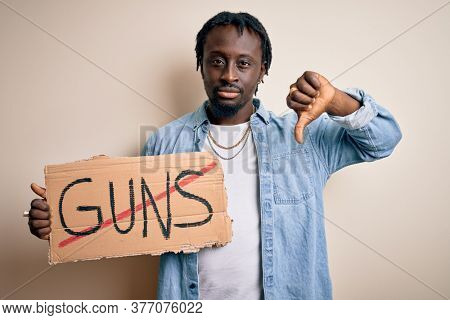 Young african american man asking for peace holding banner with prohibited guns message with angry face, negative sign showing dislike with thumbs down, rejection concept