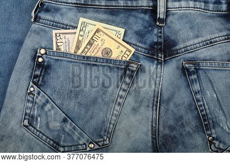 Close Up Several Different Value Us Dollar Paper Currency Banknotes In Jeans Back Pocket, Low Angle