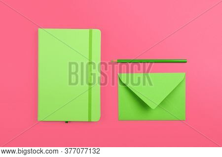 Neatly Organized Stationery Flat Lay Of Pastel Green Notebook, Envelope And Pencil Over Pink Paper B
