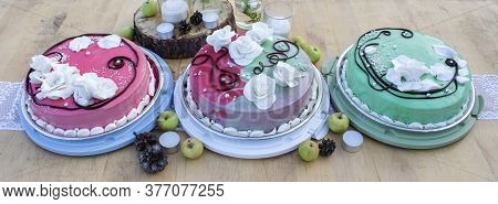 Three Wedding Cakes On A Wooden Table Surrounded By Candles, Pine Cones, Apples And Other Wedding Pa