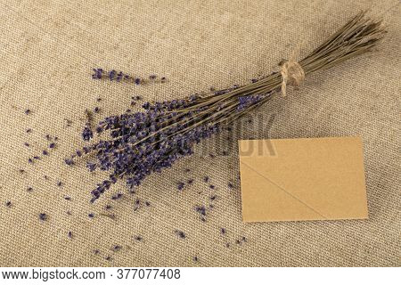 Close Up Bouquet Of Dried Lavender Flowers And Small Blank Paper Note Message On Brown Canvas Tablec