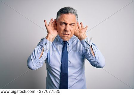 Middle age handsome grey-haired business man wearing elegant shirt and tie Trying to hear both hands on ear gesture, curious for gossip. Hearing problem, deaf