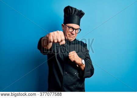 Middle age handsome grey-haired chef man wearing cooker uniform and hat Punching fist to fight, aggressive and angry attack, threat and violence