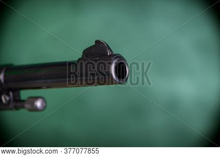 A Revolver Is Aiming Past The Frame Against Green Background. Focus On The Muzzle, The Rest Is Blurr