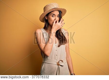 Young beautiful brunette woman on vacation wearing casual dress and hat smelling something stinky and disgusting, intolerable smell, holding breath with fingers on nose. Bad smell