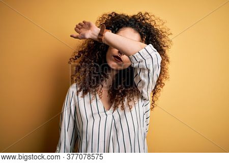 Young beautiful woman with curly hair and piercing wearing striped shirt and glasses covering eyes with arm, looking serious and sad. Sightless, hiding and rejection concept