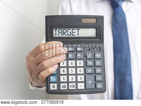 Target Word On Calculator Screen In Hands Of Businessman In Shirt And Tie. Going To Target Or Reachi