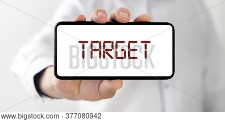 Target Word On White Phone Screen In Hands Of Businessman In Shirt. Going To Target Or Reaching Targ