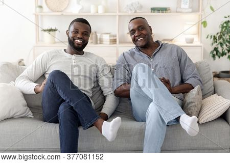 Like Father Like Son. Happy Black Millennial Man Sitting In Similar Pose On Couch With His Dad, Smil