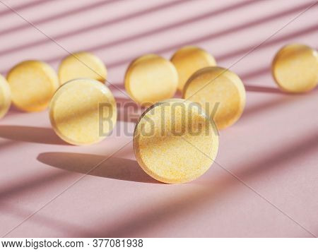 Heap Of Soluble Effervescent Vitamin Tablets On Shadow Pink Paper Background. Vitamins And Nutrition