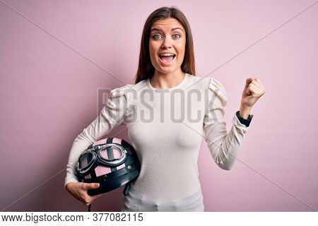 Young beautiful motorcyclist woman with blue eyes holding moto helmet over pink background screaming proud and celebrating victory and success very excited, cheering emotion