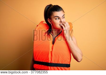 Young beautiful brunette woman wearing orange safe lifejacket over yellow background looking stressed and nervous with hands on mouth biting nails. Anxiety problem.