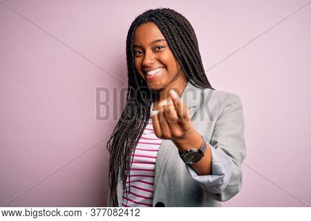 Young african american business woman standing over pink isolated background Beckoning come here gesture with hand inviting welcoming happy and smiling