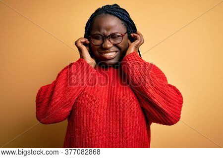 African american plus size woman with braids wearing casual sweater over yellow background covering ears with fingers with annoyed expression for the noise of loud music. Deaf concept.