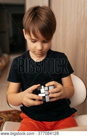 Concentrated Boy Making A Moving Cube With Fingers While Sitting At His Table In His Room