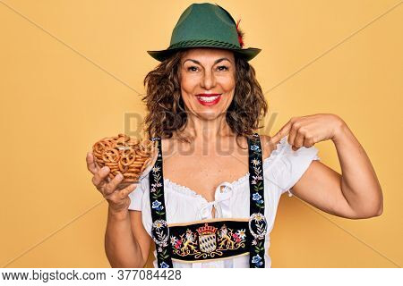 Middle age woman wearing traditional octoberfest dress holding bowl with baked pretzels with surprise face pointing finger to himself