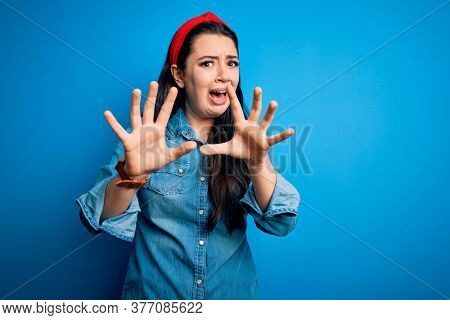 Young brunette woman wearing casual denim shirt over blue isolated background afraid and terrified with fear expression stop gesture with hands, shouting in shock. Panic concept.