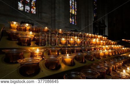Candles Burn Inside Church, Close View Of Candles In Dark Cathedral Interior. Concept Of Faith, Pray