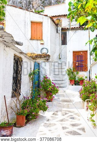 Old Narrow Street With Flowers In Anafiotika, Plaka District, Athens, Greece. Plaka Is Tourist Attra