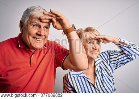 Senior beautiful couple standing together over isolated white background very happy and smiling looking far away with hand over head. Searching concept.