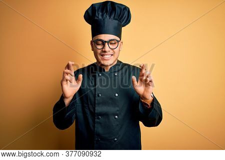 Young brazilian chef man wearing cooker uniform and hat over isolated yellow background gesturing finger crossed smiling with hope and eyes closed. Luck and superstitious concept.
