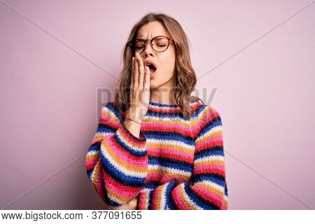 Young beautiful blonde girl wearing glasses and casual sweater over pink isolated background bored yawning tired covering mouth with hand. Restless and sleepiness.