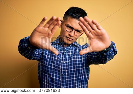 Young handsome latin man wearing casual shirt and glasses over yellow background doing frame using hands palms and fingers, camera perspective