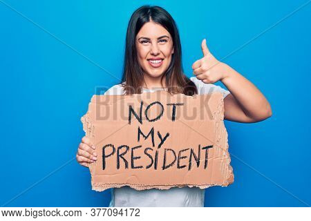 Young beautiful woman on disagreement holding banner with not my president message smiling happy and positive, thumb up doing excellent and approval sign