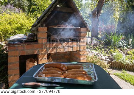 Barbeque Grill Fireplace Int He Garden. Grilling Sausages And Meat On Barbecue Grill.