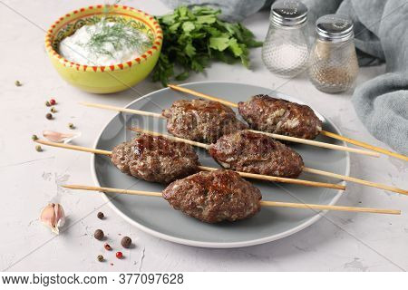 Kofta Kebab On Wooden Skewers On A Plate And Sauce On The Table, Traditional Dish Of Arab Cuisine, G