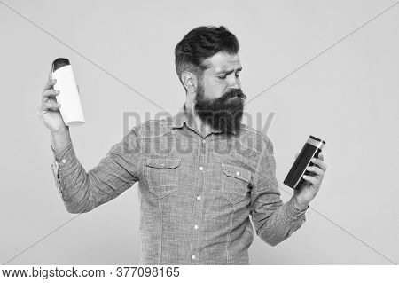 Bath Cosmetics Review. Man Bearded Hipster Hold Plastic Bottles. Hair Care. Skin Lotion. Picking Pro