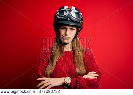 Young beautiful redhead motocyclist woman wearing moto helmet over red background skeptic and nervous, disapproving expression on face with crossed arms. Negative person.