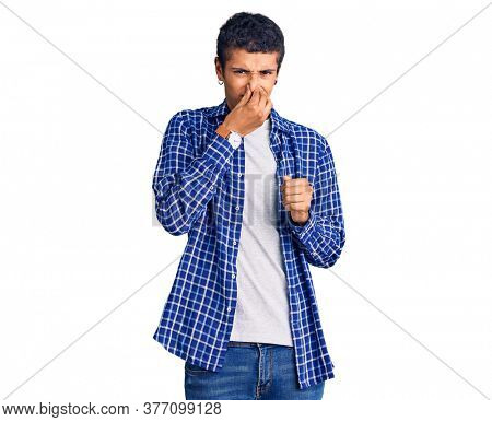 Young african amercian man wearing casual clothes smelling something stinky and disgusting, intolerable smell, holding breath with fingers on nose. bad smell