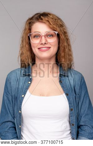 Pleasant Smart Young Female In Casual Outfit And Trendy Eyeglasses Looking At Camera And Smiling Fri