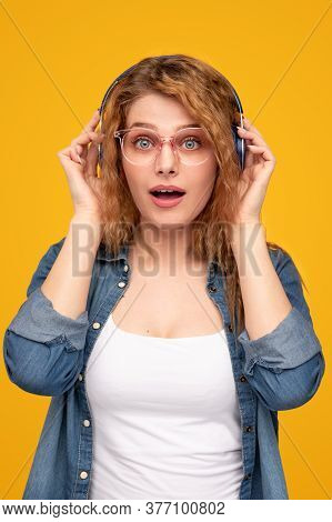 Astonished Blond Female In Glasses Adjusting Headphones And Looking At Camera With Opened Mouth Whil