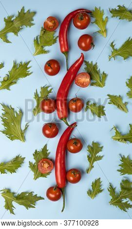 Red Chili Peppers, Tomatoes And Green Rucola Salad Leaves On Blue Background.