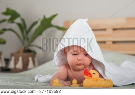 Newborn Baby In A White Towel. Baby And Bathing. Small Child Care, Bathing, Ducks.