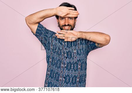 Young handsome hispanic bohemian man wearing hippie style over pink background Smiling cheerful playing peek a boo with hands showing face. Surprised and exited