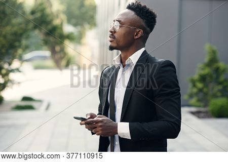 Serious Black Businessman Texting On Smartphone Outdoors. Young African-american Salesman Working Wi