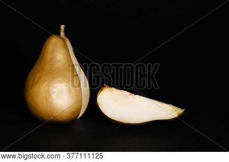 Golden Pear With A Cut Wedge On A Black Background, Art Deco Fruit.