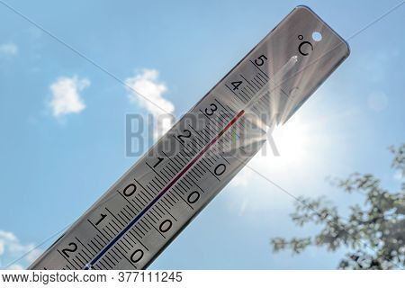 Thermometer Shows Heat In The Summer Season Against A Blue Sky With Sunbeams And Lens Flares, Weathe