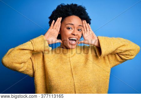 Young beautiful African American afro woman with curly hair wearing yellow casual sweater Smiling cheerful playing peek a boo with hands showing face. Surprised and exited