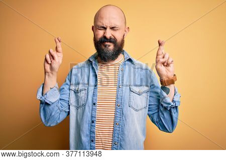 Handsome bald man with beard wearing casual denim jacket and striped t-shirt gesturing finger crossed smiling with hope and eyes closed. Luck and superstitious concept.