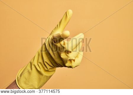 Hand of caucasian young man with cleaning glove over isolated yellow background pointing forefinger to the camera, choosing and indicating towards direction