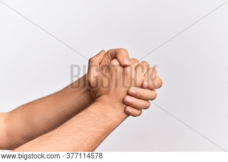 Hand of caucasian young man showing fingers over isolated white background with both hands crossed together showing strength and confidence