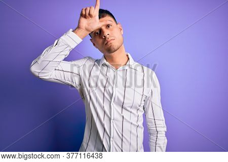 Young handsome hispanic man wearing elegant business shirt standing over purple background making fun of people with fingers on forehead doing loser gesture mocking and insulting.
