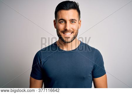 Young handsome man wearing casual t-shirt standing over isolated white background with a happy and cool smile on face. Lucky person.