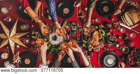Flat-lay Of Family Clinking Glasses At Christmas Table, Wide Composition