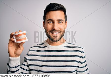 Young handsome man with beard holding plastic denture teeth over white background with a happy and cool smile on face. Lucky person.